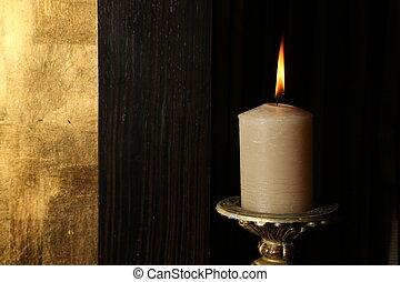 Burning candle on retro candlestick. Close up