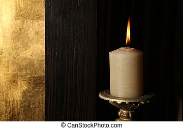Burning candle on retro candlestick. Close up