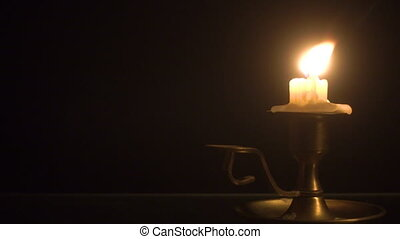 Burning candle on the brass candlestick over black...