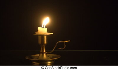 Burning candle on the old brass candlestick over black...