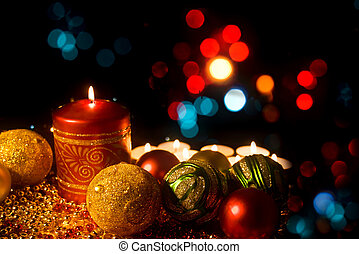 Burning candle with Christmas-tree decorations