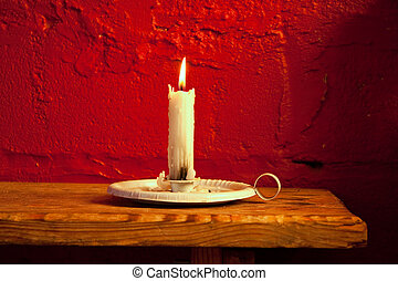 burning candle - single white wax candle burning in old...