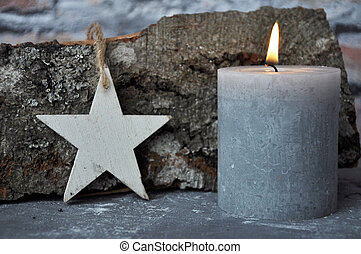 Burning candle, star and wood billet on concrete