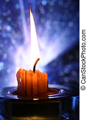 Burning candle - The image of burning candle on a dark blue...