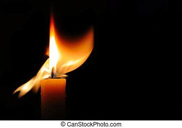 Burning candle - Beautifully burning candle on a black...