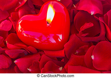 burning candle with rose petals