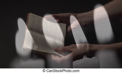 Animation of person praying and holding Bible and candles being blown off. Religion faith tradition nature concept digitally generated image.