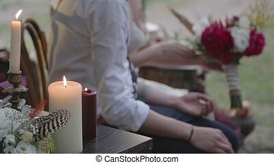 Burning candles and a couple holding hands