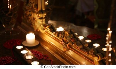 Burning candles and beads face a mirror in carved frame