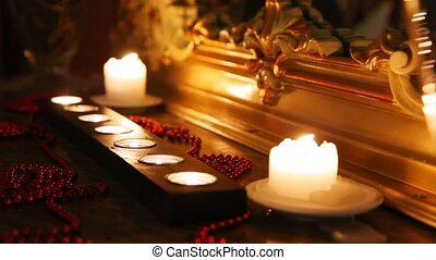 Burning candles and beads face mirror in carved frame in...
