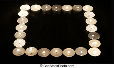 Burning candles are laid out in the form of a square.
