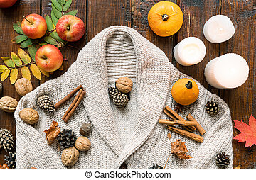Burning candles, harvest, spices, nuts, leaves and firtree cones on warm sweater