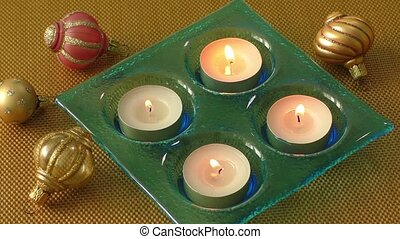 Burning candles in a Christmas setting with seasonal...