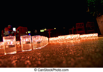 Burning candles in glass flasks stand on the floor of celebraiotn hall. Background.