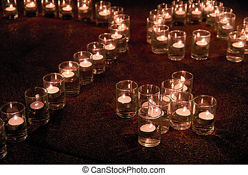 Burning candles in glass flasks stand on the floor of celebraiotn hall.