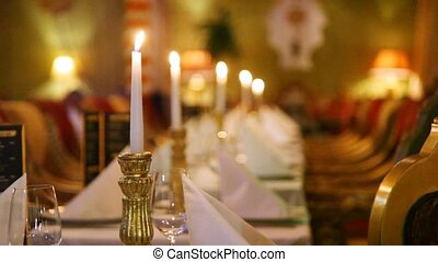 Burning candles in row stand on tables with white cloths