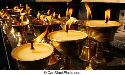 Burning candles in temple. View of golden shiny bowls with burning flame of oil candles for worship.
