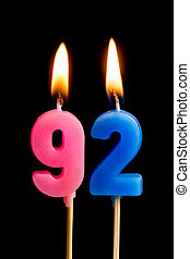 Burning candles in the form of 92 ninety two (numbers,...