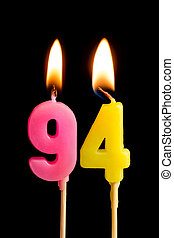 Burning candles in the form of 94 ninety four (numbers,...