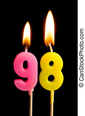 Burning candles in the form of 98 ninety eight (numbers,...