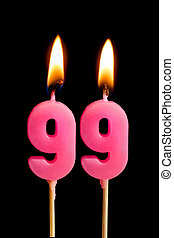 Burning candles in the form of 99 ninety nine (numbers,...