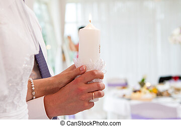 burning candles in the hands of the newlyweds