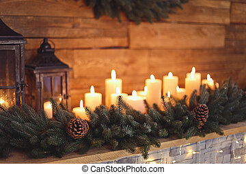 Burning candles in the New Year's interior with a Christmas fireplace
