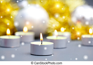 burning candles on a background of Christmas balls
