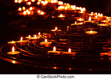 Rows of burning candles in a cathedral