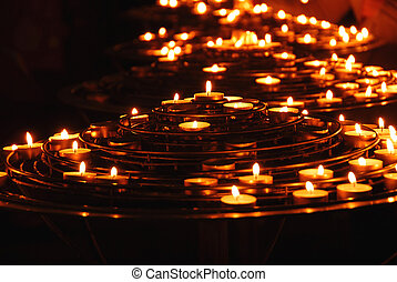 Burning candles - Rows of burning candles inside a cathedral