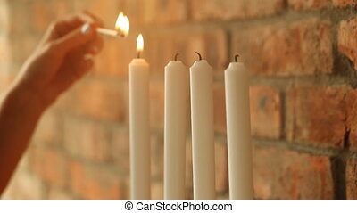 Burning candles on a brick wall background