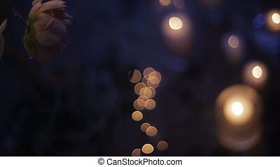 Burning candles through white branches of a tree decorated with roses. Christmas holidays