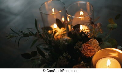 Burning candles with beautiful bouquet of different flowers...