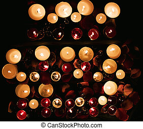 Burning candles with petals of roses