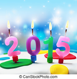 burning candles with the symbol of the new year 2015 on the cake