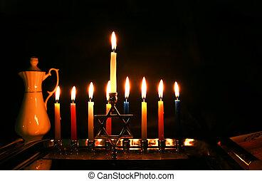 Burning Chanukah. The lit Chanukiah. Jewish holiday Hanukkah. Porcelain jug with oil