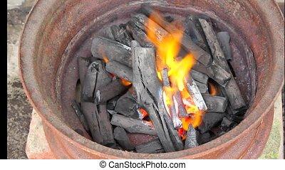 burning charcoal in metal rim