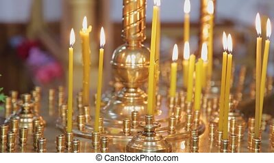 Burning church candles on a candlestick during church services