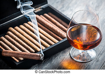 Burning cigar and cognac in glass
