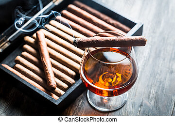 Burning cigar on humidor and cognac in glass