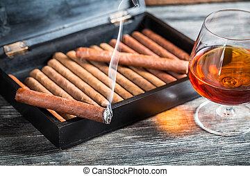 Burning cigar on humidor and cognac