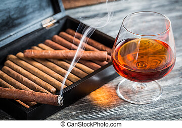 Burning cigar on humidor and cognac