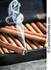 Burning cigar on wooden humidor full with cigars