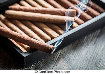 Burning cigar on wooden humidor
