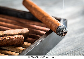 Burning cigar with smoke on wooden humidor