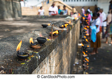 Burning clay oil lamp offerings with bright fire in a temple