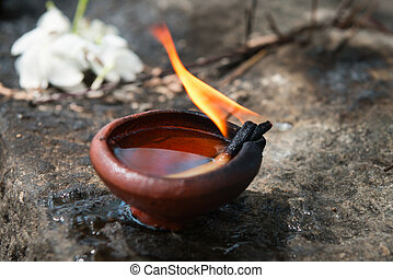 Burning clay oil lamp with white flowers a buddhist and hindu temple