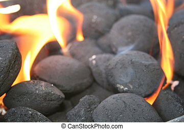 Black coal engulfed in hot orange flames, emiting gray smoke.