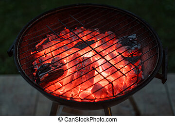 Burning coals and sparks coming out of the barbecue. BBQ brazier with sparks.