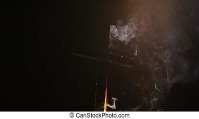 Burning cross falling down with smoke in the darkness of night